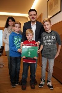 Yannick, Aurélie und Lea Powileit überreichen Bürgermeister Greiber das Erste Kids Climate Conference Buch